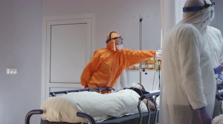 поворотный : Doctor in Orange Protective Suit Turning On Coronavirus Pateints Heart Monitor - Wide Dolly Shot