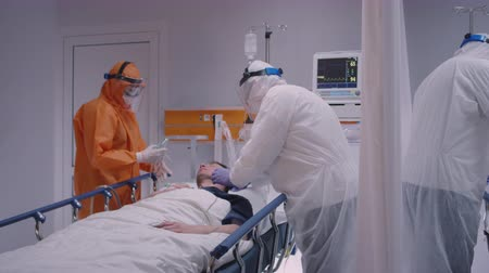 longen : Doctor in Protective Suit Putting on Oxygen Mask on Patient Suffering from Coronavirus - Wide Slow Motion Dolly Shot