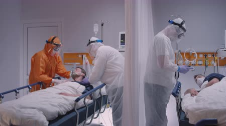 protective suit : Doctor in Protective Suit Putting on Oxygen Mask on Patient Suffering from Coronavirus - Wide Slow Motion Dolly Shot
