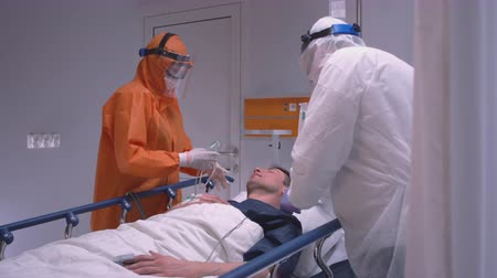 protective suit : Doctors in Protective Suit Putting on Oxygen Mask on Patient Suffering from Coronavirus - Wide Slow Motion Dolly Shot