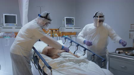 oxigênio : Doctor in Protective Suit Puttig on Oximeter on Coronavirus Patients Finger - Wide Slow Motion Dolly Shot