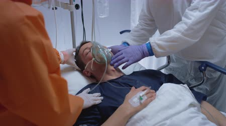 Doctors in Protective Suits Putting on Oxygen Mask on Coronvarius Patients Face - Medium Shot in Slow Motion