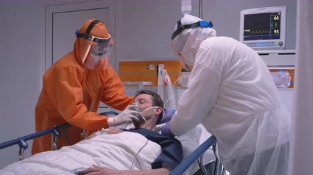 Doctors in Protective Suit Putting on Oxygen Mask on Patient Suffering from Coronavirus - Wide Slow Motion Dolly Shot