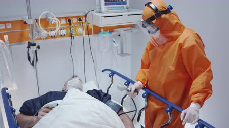 respiratory infection : Doctor in Protective Suit Measuring Coronavirus Patients Blood Pressure - Wide Shot