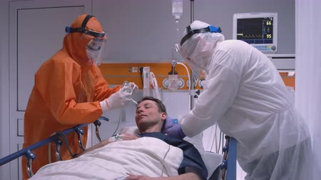 longen : Doctor in Protective Suit Putting on Oxygen Mask on Patient Suffering from Coronavirus - Wide Dolly Shot Stockvideo