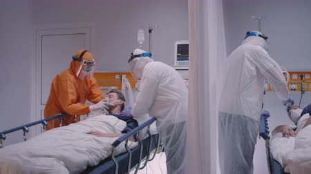 respiratory infection : Doctor in Protective Suit Putting on Oxygen Mask on Patient Suffering from Coronavirus - Wide Dolly Shot Stock Footage