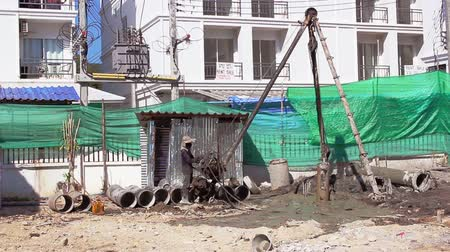 bailer : PHUKET THAILAND CIRCA FEB 2015: Workers work at well drilling in village Kamal Phuket. Many migrants from neighbouring countries do the heavy lifting Stock Footage