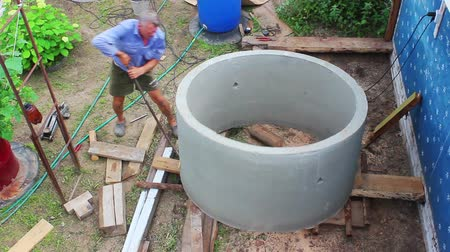 poça de água : Person transpose of the concrete parts alone and manually. Builds water well Stock Footage