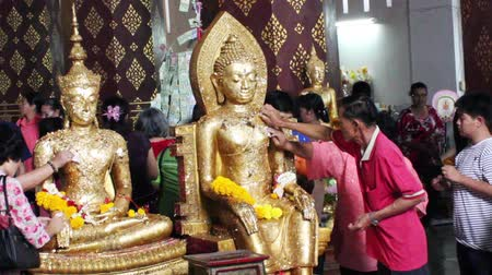 budist : AYUTTHAYA, THAILAND - FEB 21, 2015: Most important Buddhist ritual - pasting gold plates on statue of Buddha. Gold leaves glued one on top of another, creating a thick layers of monolithic gold Stok Video