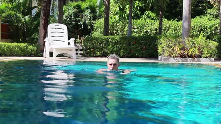 An older spa Visitor swimming in a swimming pool on holiday