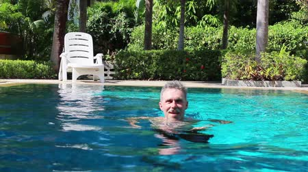 Happy older man swimming in a small swimming pool