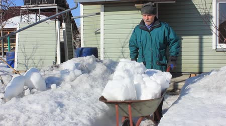 Elderly man clears a country house from snow. End of winter