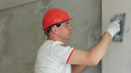 Repairman aligns the wall in the room. Repairs in the living room