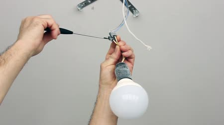 Electrician turns off the temporary lamp in the repaired room