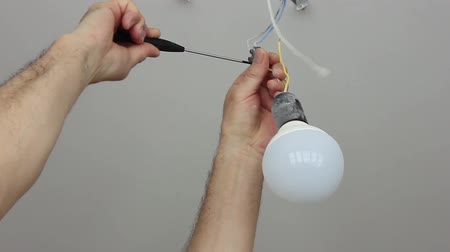 Electrician connects a temporary lamp in the repaired room Stock Footage