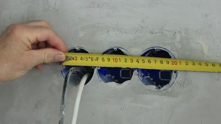 dimensão : The builder works on repairing the premises, uses a tape measure