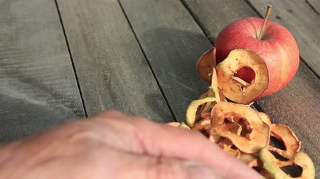 encanecido : Farmer pours a handful of dried apples on the old table