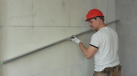 The worker controls the quality of the construction of the partition Stock Footage