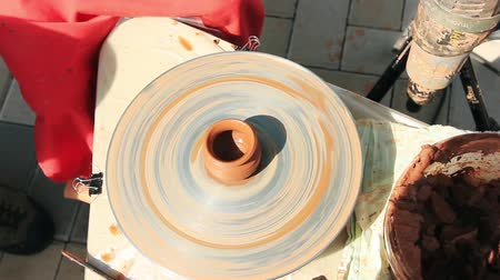 Child is learning to work on a potter wheel, working with clay