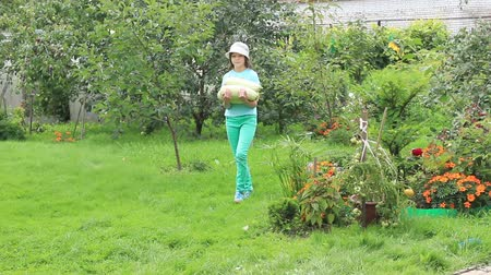 Girl carries several vegetable marrows in hands, moving on garden. Middle of august Stock Footage