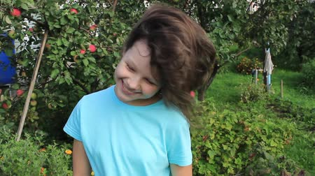 Teen girl demonstrates her hair on a background of orchard