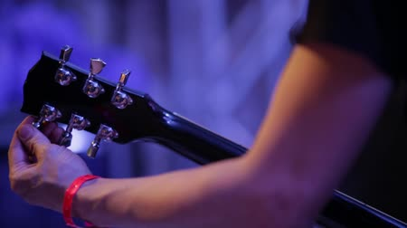 настройка : Medium shot of musicians arm tuning electric guitar backstage at concert