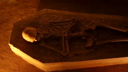 mroczne : Skeleton laid down in a tomb inside a dark cave with orange tones in lighting