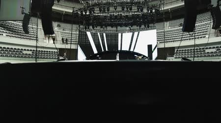 talapzat : Pedestal shot that moves up to a stage to show lights and sound set-up before a concert.  Black, white and gray tones Stock mozgókép