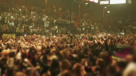 koncert : Shot of unrecognizable crowd of people cheering at a concert.  You can also see people on the stands of the Coliseum.