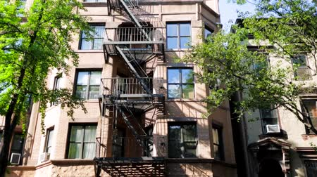 exterior : Daytime establishing shot of a building in Brooklyn with emergency staircase in front of the building
