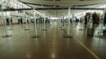 иммиграция : Shot at check-in area at an airport.  There are unrecognizable people walking around and no one making the lines.  Clear light. Стоковые видеозаписи