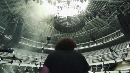 davulcu : A man playing the drums at an empty Coliseum.  The shot was taken from behind him on the stage.  Stok Video