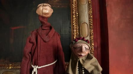 loutka : Pan of two puppets dressed as monks.  Shot end with a piece of art on a large frame