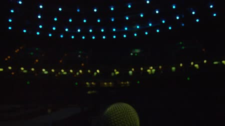 концерт : View of microphone from the stage.  Green and blue lights. No people