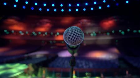 koncert : Close up of a microphone on a stage, taken from the stage.  Different spotlight colors on the microphone and then zoom out to see empty auditorium with yellow, red, blue and green spotlights.