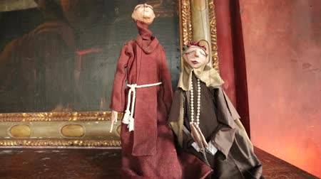 долл : Tilt up of two puppets dressed as monks in front of large framed art