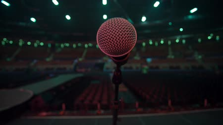 czerwone tło : Microphone on stage before a concert.  Main focus is the microphone which has some tones of red.  Empty auditorium. No people. View from the stage