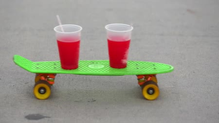 komik : A shot of a skateboard passing by with two red drinks on top.  No person can be seen in the shot.