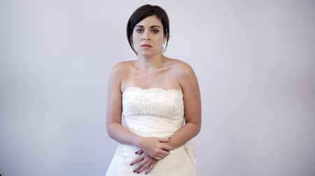 esküvő : Shot of a bride indoors as she shows emotion of sadness and insecurity.  White background in studio