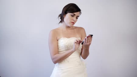 be sad : Indoor, studio shot of a bride to be on her wedding dress, impatiently texting on her cellphone.