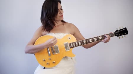 kytara : Shot in studio of a beautiful bride playing an electric guitar on her wedding dress.  White background Dostupné videozáznamy