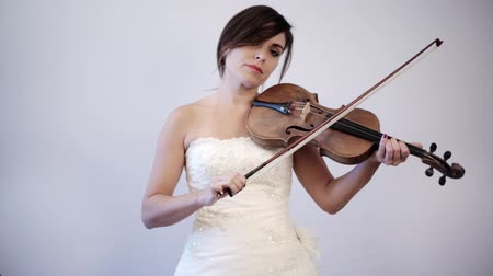 houslista : Indoor shot in a studio of a woman showing feelings of disappointment and sadness while playing the violin on her wedding dress.