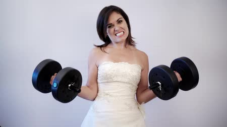 сильный : Indoor, studio shot of woman trying to lift heavy weights as she wears her wedding dress.