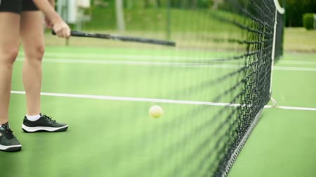 match : Daytime shot of unrecognizable woman bouncing a tennis ball with racket inside of tennis court.  It is a medium shot so you only see her legs and arm. Stock Footage