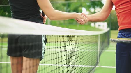 ракетка : Daytime shot of a female and a male tennis player as they shake hands by the net.  At the beginning of the shot you only see the net.  The faces cannot be seen in the shot. Стоковые видеозаписи