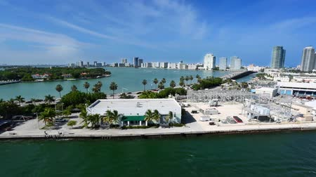 ostrovy : Long traveling shot from the water of Miami. Palm trees, buildings and water can be seen in the shot on a beautiful day. Dostupné videozáznamy