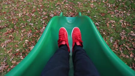fall down : Shot taken from behind of unrecognizable person coming down a slide into beautiful fall leaves