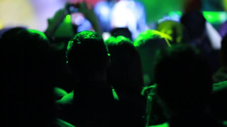 kibice : Close-up Shot from behind of a crowd of people at a concertshow.  The unrecognizable people on the shot are taking pictures.  Cool lighting on the shot. Wideo