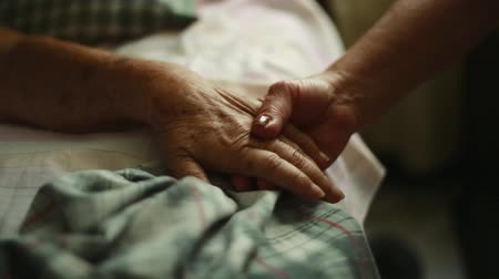 régi : Close-up Pan of Unrecognizable Elderly person holding hands with another person to the bed where she is lying down Stock mozgókép