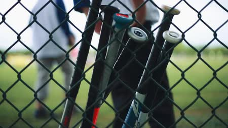 klatka : Baseball Bats leaning against a Fence at Baseball Park with unrecognizable people around